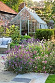 THE COACH HOUSE, SURREY: GREENHOUSE AND PAVED SEATING AREA WITH BORDER OF ERYSIMUM BOWLES MAUVE, CISTUS X ARGENTUS SILVER PINK, GERANIUM ORION & LUZULA NIVEA.SUMMER,GARDEN.