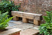 THE COACH HOUSE, SURREY: RUSTIC OAK BENCH WITH 2015 ENGRAVING ON PAVED AREA. STONE, WOOD, HANDMADE, TRADITIONAL, SEAT, SEATING.