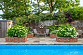 THE COACH HOUSE, SURRY:WALLED SWIMMING POOL AREA WITH RAISED BRICK BEDS CONTAINING HYDRANGEA ARBORESCENS ANNABELLE. SUMMER, A PLACE TO SIT,TABLE & CHAIRS,ENTERTAIN,LEISURE,GARDEN