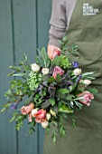 THE REAL FLOWER COMPANY:GIRL/WOMAN HOLDING BEAUTIFUL FLORAL POSY/ARRANGEMENT WITH ROSA CAFFE LATTE AND PAVLOVA. ALSO WITH PURPLE AND SILVER LAVENDER,MIXED SAGE AND SENECCIO