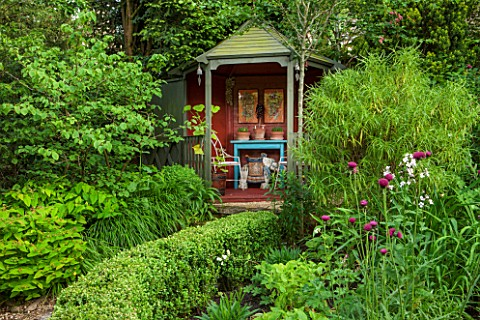 THE_LODGE_BURFORD_OXFORDSHIRE_TEA_HOUSE_IN_LUSH_GREEN_GARDEN_PLANTED_WITH_BOX_YEW_HEBE_HAKONECHLOA_M