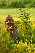 GREYHOUNDS, BURFORD, OXFORDSHIRE: OLD LIDDED TERRACOTTA JARS/URNS IN MEADOW. INFORMAL STYLE