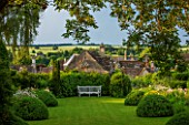 GREYHOUNDS, BURFORD, OXFORDSHIRE: COTTAGE STYLE LAWN AND BORDER WITH WOODEN BENCH. BOX DOMES, YEW TOPIARY, SUNLIGHT. CLASSIC COUNTRY GARDEN, SUMMER.