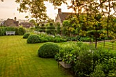 GREYHOUNDS, BURFORD, OXFORDSHIRE: CLASSIC COUNTRY GARDEN WITH LAWN, BOX DOMES AND YEW TOPIARY. BORDERS WITH COTTAGE GARDEN PLANTS. BENCHES. A PLACE TO SIT. SUMMER
