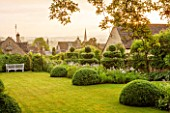 GREYHOUNDS, BURFORD, OXFORDSHIRE:DAWN LIGHT ON CLASSIC COUNTRY GARDEN WITH LAWN, BOX DOMES AND YEW TOPIARY. BORDERS WITH COTTAGE GARDEN PLANTS. WOODEN BENCH. A PLACE TO SIT. SUMMER