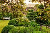 GREYHOUNDS, BURFORD, OXFORDSHIRE: VIEW ONTO CLASSIC COUNTRY GARDEN WITH BOX DOMES AND YEW TOPIARY. BORDERS WITH COTTAGE GARDEN PLANTS. WOODEN BENCH. A PLACE TO SIT. SUMMER
