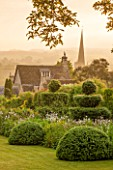 GREYHOUNDS, BURFORD, OXFORDSHIRE: CLASSIC COUNTRY GARDEN WITH BOX DOMES AND YEW TOPIARY. DAWN LIGHT, SUMMER, BORDERS WITH COTTAGE GARDEN PLANTS.