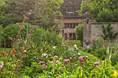 PYTTS PLACE, BURFORD: DAWN LIGHT ON VISTA FROM FOUNTAIN TO QUADRUPLE PERENNIAL BORDERS WITH FOXGLOVES, PEONIES, ALCHEMILLA MOLLIS, STACHYS BYZANTINA,AQUILEGIAS AND GRASSES