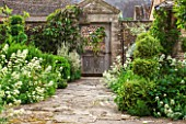 OXLEAZE FARM, OXFORDSHIRE: STONE PAVED PATH LEADING TO OLD WOODEN & RUSTED METAL ORNATE GARDEN GATE WITH CENTRANTHUS RUBER ALBUS (WHITE VALERIAN) & VARIGATED BOX TOPIARY SHAPES