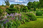 GREYHOUNDS, BURFORD, OXFORDSHIRE:COUNTRY GARDEN & COTTAGE BORDER WITH VALERIANA OFFICINALIS, CAMPANULA VARS & ERYNGIUM BOURGATII. WITH BOX DOMES & YEW TOPIARY. SUMMER, LILAC,PURPLE