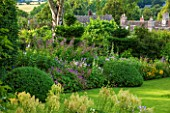 GREYHOUNDS, BURFORD, OXFORDSHIRE:COUNTRY COTTAGE BORDER WITH HERBACOUS PERENNIALS INCLUDING PHLOX, GERANIUMS, EUPHORBIA, HOLLYHOCKS, CAMPANULA & BOX DOMES. SUMMER, INFORMAL GARDEN.