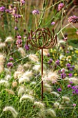 ANNE GODFREYS PRIVATE GARDEN, HERTFORDSHIRE. OWNER OF DAISY ROOTS NURSERY. RUSTY METAL ALLIUM SCULPTURES AMONGST PENNISETUM. ORNAMENT, DECORATION, DECORATIVE