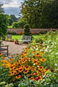 KELMARSH HALL, NORTHAMPTONSHIRE: BORDER IN WALLED GARDEN WITH RUDBECKIA HIRTA, WHITE COSMOS & DAHLIA MOOR PLACE. GRAVEL SEATING AREA, TOPIARY SPIRAL. LATE SUMMER.