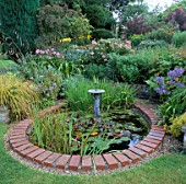 BRICK EDGED POND LITTLE BOY FOUNTAIN  DENDRANTHEMA CLARA CURTIS  IRIS LAEVIGATA SNOW DRIFT.  VALE END  SURREY