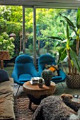 ABIGAIL AHERN HOUSE, LONDON: THE LIVING ROOM AND VIEW ONTO PATIO - BLUE CHAIRS, INSIDE OUT. CUSHIONS, SITTING ROOM, DARK, INTERIOR, NILE OTTOMAN STOOL, FAKE GOLDENBALL CACTUS