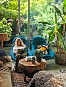 ABIGAIL AHERN HOUSE, LONDON: ABIGAIL AHERN READING IN THE LIVING ROOM - BLUE CHAIRS, NILE OTTOMAN STOOL, FAKE GOLDENBALL CACTUS, PATIO OUTSIDE, INSIDE OUT
