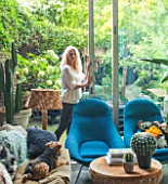 ABIGAIL AHERN HOUSE, LONDON: ABIGAIL AHERN IN THE LIVING ROOM - BLUE CHAIRS, NILE OTTOMAN STOOL, FAKE GOLDENBALL CACTUS, PATIO OUTSIDE, INSIDE OUT, SETTEE, MAUD THE DOG, PET