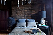 ABIGAIL AHERN HOUSE, LONDON: BEDROOM PAINTED IN CROSBY - MAUD THE DOG ON BED, PILLOWS, HAGUE WOODEN BEADED CHANDELIER, DARK, ROOM, INTERIOR, THROW
