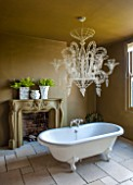 ABIGAIL AHERN HOUSE, LONDON: BATHROOM PAINTED WITH WOOSTER OLIVE PAINT, BATH, FIREPLACE, FAUX PLANTS, NEO - BAROQUE CHANDELIER