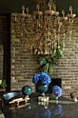 ABIGAIL AHERN HOUSE, LONDON: THE DINING ROOM - CHANDELIER, DARK, INTERIOR, HYDRANGEAS, CONTAINER, VASE, WALL