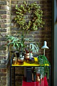 ABIGAIL AHERN HOUSE, LONDON: THE DINING ROOM - DARK, INTERIOR, WALL, BERRY WREATH, DECORATION, STAGHORN PLANT, DRINKS TABLE