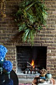 ABIGAIL AHERN HOUSE, LONDON: THE DINING ROOM - DARK, INTERIOR, WALL, DECORATION, GREEN WREATH, WALL, FIREPLACE, BLUE, HYDRANGEA