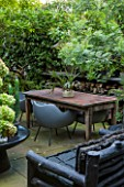 ABIGAIL AHERN HOUSE, LONDON: GARDEN, PATIO WITH TABLE, CHAIRS, FAUX STAGHORN PLANT IN CONTAINER, OUTDOOR KITCHEN