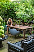 ABIGAIL AHERN HOUSE, LONDON: ABIGAIL IN HER GARDEN, PATIO WITH TABLE, CHAIRS, FAUX STAGHORN PLANT IN CONTAINER, OUTDOOR KITCHEN