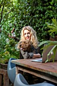 ABIGAIL AHERN HOUSE, LONDON: ABIGAIL IN HER GARDEN WITH PET DOG MAUD, PATIO WITH TABLE, CHAIRS, FAUX STAGHORN PLANT IN CONTAINER