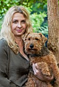 ABIGAIL AHERN HOUSE, LONDON: ABIGAIL IN HER GARDEN WITH PET DOG MAUD