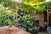 ABIGAIL AHERN HOUSE, LONDON: TOWN GARDEN WITH TABLE, CHAIRS, LIGHT, FIREPLACE, FAUX CACTUS