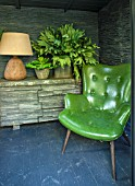 ABIGAIL AHERN HOUSE, LONDON: TOWN GARDEN. INTERIOR OF CABIN TYPE SHED. LAMP, GREEN CHAIR, SEAT, FAUX PLANTS IN CONTAINERS, FAUX SLATED WALL, DAWLISH SIDEBOARD WITH STONE FACADE