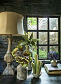 ABIGAIL AHERN HOUSE, LONDON: TOWN GARDEN. INTERIOR OF CABIN TYPE SHED. LAMP, FAUX PLANTS IN CONTAINERS, FAUX SLATED WALL, WINDOW