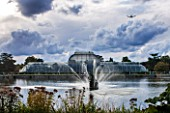 ROYAL BOTANIC GARDENS, KEW: FOUNTAIN, LAKE AND VICTORIAN PALM HOUSE IN AUTUMN - AFTERNOON LIGHT, IRON, GLASS, WATER, ORNAMENT, SKY, DRAMATIC