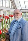 GUERNSEY NERINE FESTIVAL: NERINE EXPERT ANDREW LANOE WITH NERINE SARNIENSIS IN THE LOWER GLASSHOUSE, CANDIE GARDENS. GUERNSEY LILY
