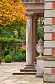 MORTON HALL, WORCESTERSHIRE: DETAIL OF SANDSTONE COLUMNS AND LIDDED URNS WITH BOX BALLS AND TREE IN AUTUMN COLOUR