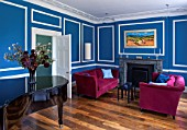 MORTON HALL, WORCESTERSHIRE: LIVING ROOM PAINTED AZURE BLUE. 18TH CENTURY FIRE SURROUND IN ITALIAN MARBLE. STEINWAY BABY GRAND PIANO, MAGENTA VELVET SOFAS BY DONGHIA
