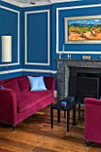 MORTON HALL,WORCESTERSHIRE:LIVING ROOM IN AZURE BLUE.18TH CENTURY FIRE SURROUND IN ITALIAN MARBLE. MAGENTA VELVET SOFAS BY DONGHIA.PAINTING VINEYARD NEAR ST JEAN PLA DE CORT