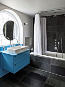 MORTON HALL, WORCESTERSHIRE: BATHROOM WITH ARCHED WINDOW, FREE STANDING CIRCULAR MIRROR WITH BLUE PAINTED CABINETS AND OVAL SHOWER CURTAIN RAIL. BLACK MARBLE TILES