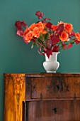 MORTON HALL, WORCESTERSHIRE: DINING ROOM. ANTIQUE CHEST OF DRAWERS WITH SMALL WHITE VASE WITH ORANGE ROSES AND FRESHLY PICKED AUTUMN MAPLE LEAF FOLIAGE
