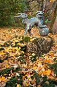 BATSFORD ARBORETUM, GLOUCESTERSHIRE. AUTUMN. OCTOBER, FALL: CHINESE FOO DOG, LION, ORNAMENT, LEAVES
