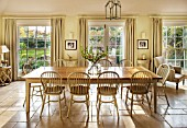THE COACH HOUSE,SURREY:BREAKFAST ROOM WITH LARGE TABLE & CHAIRS, MANDARIN STONE FLOOR, FLOOR TO CEILING SASH WINDOWS AND DOORS TO PAVED PATIO.FRENCH COUNTRY STYLE, NEUTRAL DECOR