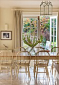 THE COACH HOUSE,SURREY:BREAKFAST ROOM WITH LARGE TABLE & CHAIRS, MANDARIN STONE FLOOR, DOORS TO PAVED PATIO.FRENCH COUNTRY STYLE, NEUTRAL DECOR