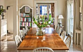 THE COACH HOUSE,SURREY:BREAKFAST ROOM WITH LARGE TABLE & CHAIRS, MANDARIN STONE FLOOR, BOOKCASE, DEMI LUNE TABLES. FRENCH COUNTRY STYLE, NEUTRAL DECOR