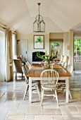 THE COACH HOUSE,SURREY:BREAKFAST ROOM WITH LARGE TABLE & CHAIRS,MANDARIN STONE FLOOR,BOOKCASE, METAL & GLASS CEILING LIGHT,WOOD BURNER.FRENCH COUNTRY STYLE, NEUTRAL DECOR