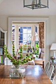 THE COACH HOUSE,SURREY: VIEW INTO GARDEN ROOM FROM BREAKFAST ROOM WITH TABLE AND CHAIRS WITH VASE OF FRESH FLOWERS/FOLIAGE