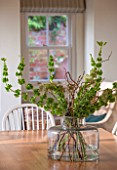 THE COACH HOUSE,SURREY: VASE OF FRESH FLOWERS/FOLIAGE ON WOODEN TABLE IN BREAKFAST ROOM
