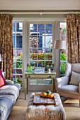 THE COACH HOUSE,SURREY: GARDEN ROOM WITH VIEW OF PATIO/LOGSTORE. SOFAS, CHAIR, SIDE TABLE, FABRIC FOOTSTOOL. COMFY, RELAXING, HOMELY, LIGHT, AIRY.