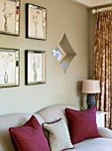 THE COACH HOUSE,SURREY: GARDEN ROOM WITH DETAIL OF NEUTRAL SOFA AND CLARET CUSHIONS. BOTANICAL PRINTS IN VENETIAN GLASS FRAMES ON WALL. DIAMOND SHAPED WINDOW