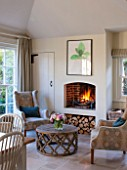THE COACH HOUSE,SURREY:THE BREAKFAST ROOM WITH ROARING LOG FIRE, COMFY ARMCHAIRS BY HUDSON HOMES & INTERIORS AND COFFEE TABLE BY OKA. COSY, RELAXING